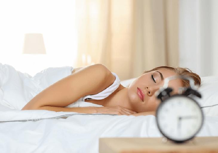 Mladá žena spí na posteli