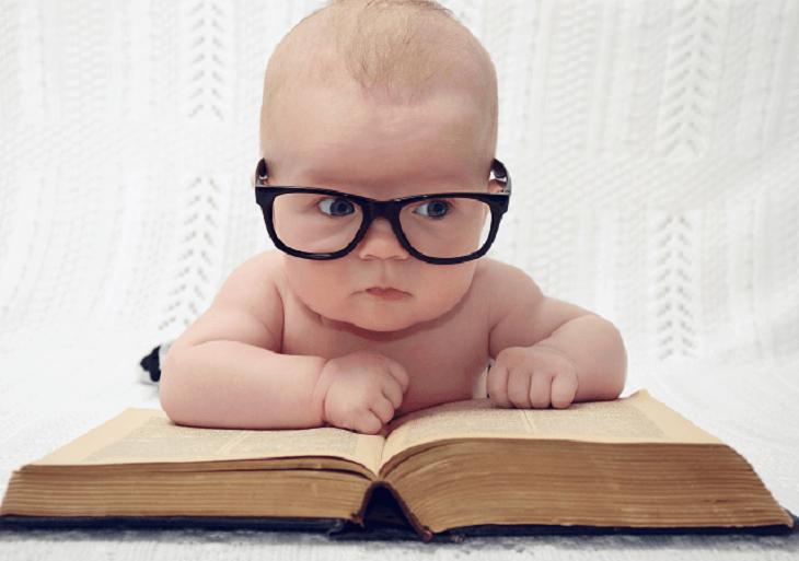 Novorodenec s okuliarmi pri knihe